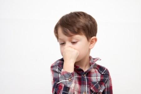 鼻を押さえる少年